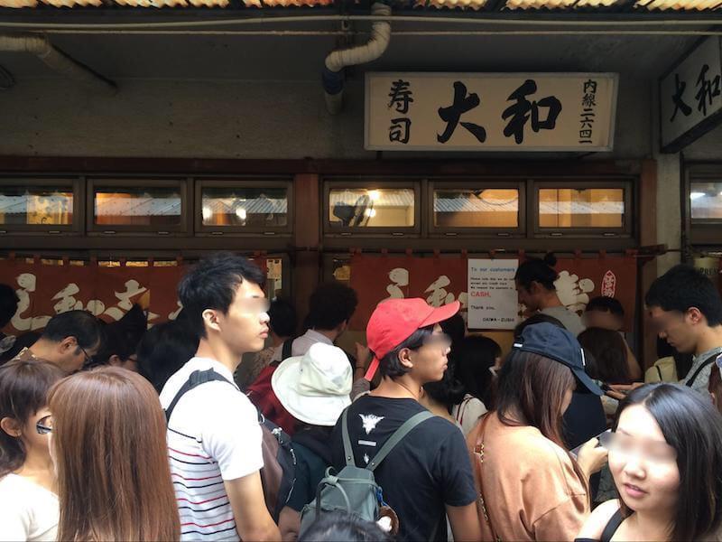 寿司屋の前に並ぶ訪日外国人